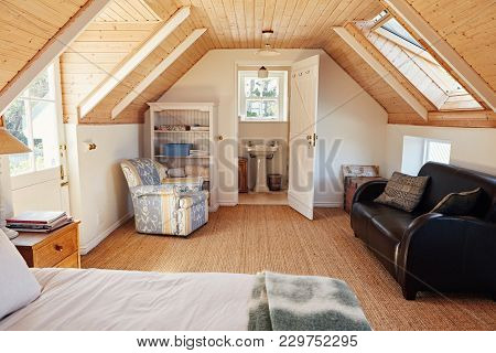Interior Of A Comfortable Master Bedroom In The Loft Of A Contemporary Residential Home With An En S