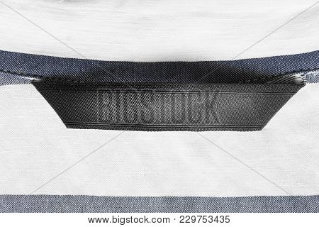 Blank Black Textile Clothes Label On Striped White And Blue Background