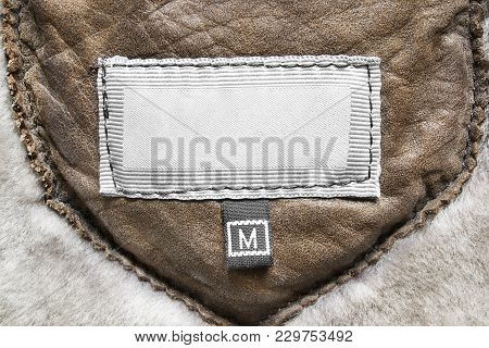 Blank Medium Size Clothes Label On Brown Leather Background Closeup