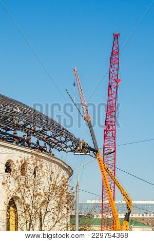 Crane And Building Construction Site Against Blue Sky. Structure Of Steel Roof Frame Installation By