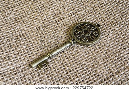 Ancient Bronze Key On Burlap. Vintage. Indoors. Horizontal Format. Color. Stock Photo.