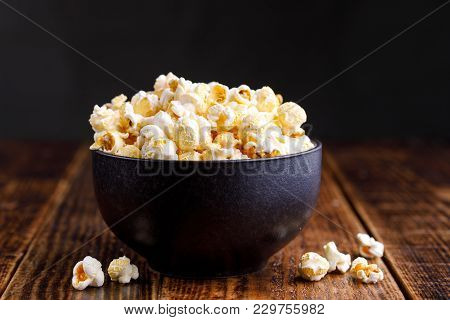 A Bowl With Popcorn On A Wooden Background.