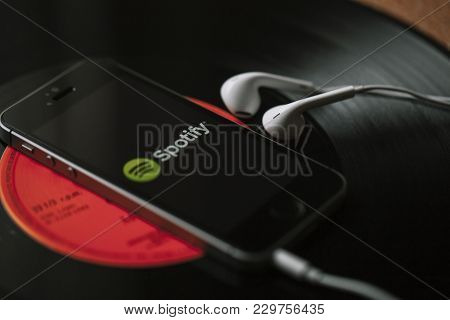 Malaga, Spain - March 5, 2018: Mobile Phone With Spotify Music Service In The Screen And White Earph