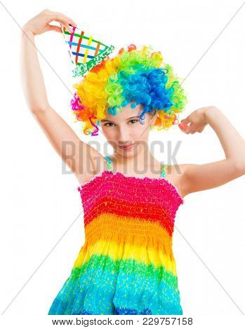Charming little girl in multicolored clown wig and birthday party hat isolated on white background