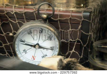 Vintage navigation compass standing upright on old treasure chest  with netting. Adventure and travel concept background.  Copy space