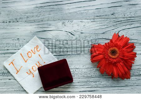 On A Wooden Background There Is A Flower In The Form Of A Heart Next To A Note With Wishes For Valen