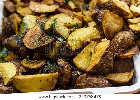 Freshly Fried Potato Wedges With Herbs And Garlic On A Baking Sheet