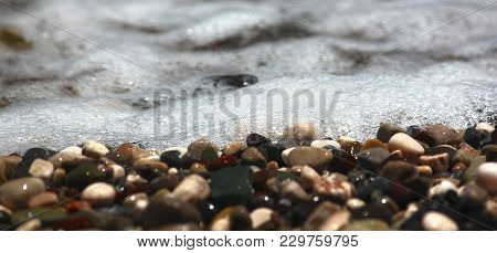 Bright Colorful Stones On The Beach With Clear Clear Water, Foamy Wave, For Banner And Texture. Focu