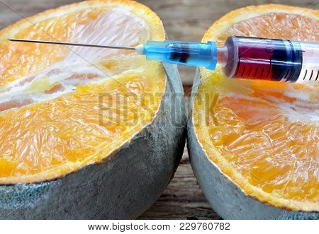 Sliced and Moldy Orange. Syringe Filled With Harmful Chemicals. Effects Of Chemicals On Fruit