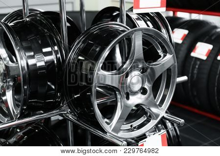 Stand with alloy wheels in modern tire store