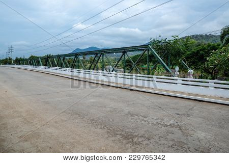 Metal Truss Beam Bridge With Concrete Road In Countryside Hill, Traveling In Thailand