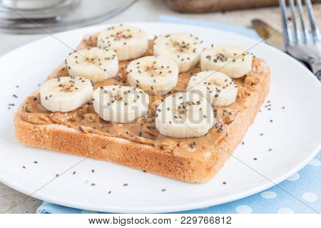 Healthy Breakfast Sandwich With Crunchy Peanut Butter, Banana And Chia Seeds, On A White Plate, Hori