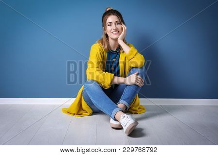 Young woman in yellow cardigan sitting near color wall
