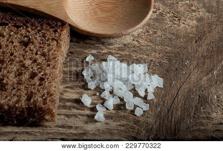 Rough Rye Bread With Coarse Salt On A Wooden Table, Macro Shot