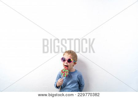 Sweets And Childhood: A Little Boy In Pink Glasses With A Round Candy In The Hands Of A White Wall