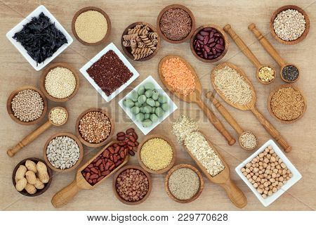 Healthy macrobiotic diet food with a selection of legumes, grains, seaweed, cereals, whole wheat pasta, seeds, wasabi and monkey nuts on hemp paper. Foods high in fibre, antioxidants and vitamins.