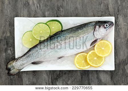 Rainbow trout health food on crushed ice with lemon and lime fruit on marble background. Very high in omega 3 fatty acid and beneficial to maintain a healthy heart.