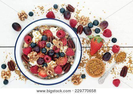 Healthy breakfast super food cereal concept with fresh fruit, granola, yoghurt, nuts and pollen grain, with foods high in protein, omega 3, antioxidants, minerals and vitamins, on rustic white wood.