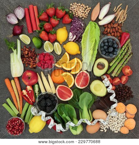 Health food for dieting concept with tape measure, fruit, vegetables  pulses, nuts, herbs, coffee and dark chocolate. Super foods high in  anthocyanins, antioxidants, fiber and vitamins. Top view.