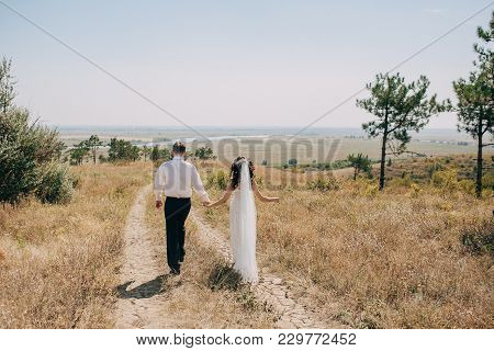 Groom In A White Shirt And The Bride In A Wedding Dress And Veil Are Holding Hands On A Sunny Hill W