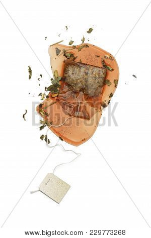 Wet Tea Bag On White Table With Herbal Mixture For Tea.