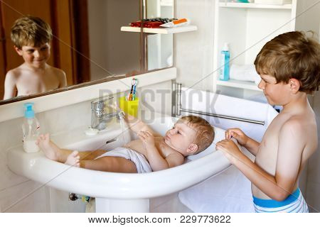 Cute Adorable Baby Taking Bath In Washing Sink And Grab Water Tap. Kid Boy Helping And Playing With