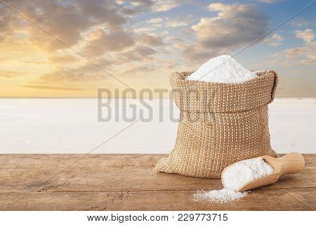Salt In Bag. Crystals Of Salt In Sack On Table With Salty Lake In The Background. Bag Of Sea Salt Pr
