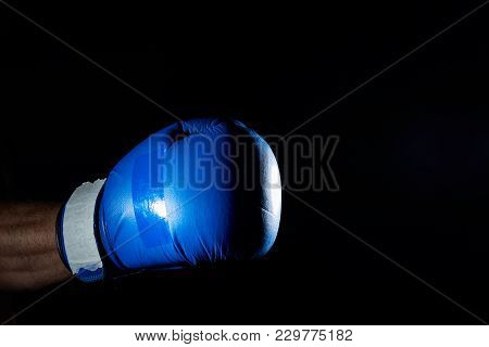 A Fighter's Blue Boxing Gloves On His Hand Isolated On Dark Blurred Background, Close-up.