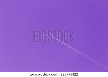 Contrail In Blue Sky. Plane, Clear Sunny Sky Ultra Violet Purple Background. Airplane Aircraft In Sk