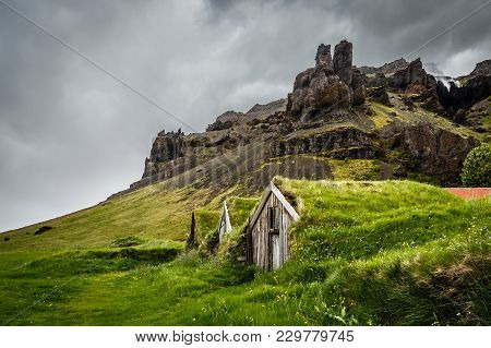 Icelandic Turf Houses Covered With Grass And Cliffs In The Background Near Kalfafell Vilage, South I