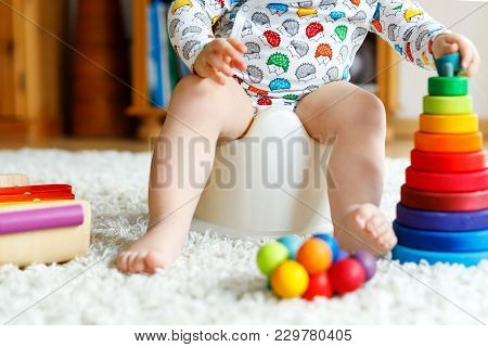 Closeup Of Cute Little 12 Months Old Toddler Baby Girl Child Sitting On Potty. Kid Playing With Educ