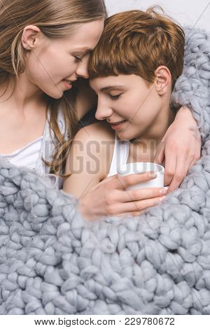 Close-up Shot Of Happy Lesbian Couple With Cup Of Coffee Embracing Under Knitted Wool Blanket