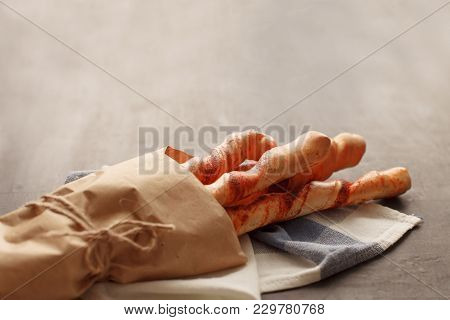 Four Baguettes In Wrapping Paper Tied With Twine Lie On White And Blue Cages Napkin, On Black Wooden