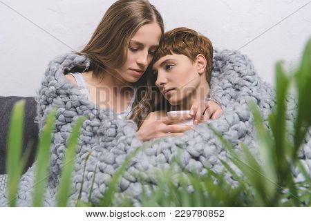 Beautiful Lesbian Couple With Cup Of Coffee Embracing Under Knitted Wool Blanket
