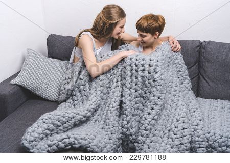 Happy Young Lesbian Couple Under Knitted Wool Blanket On Couch