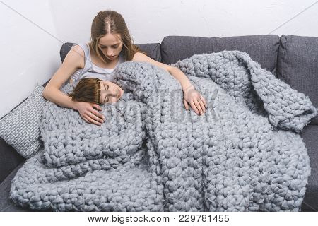 Young Lesbian Couple Relaxing Under Knitted Wool Blanket