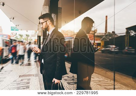Handsome Serious Young Man Entrepreneur With Beard And In Glasses Is Answering Chat Message On His S