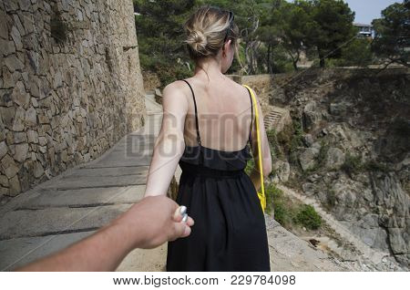 Woman With Beautiful Hair Discovering Beautiful Places Holding Boyfriend's Hand. Follow Me. Follow M