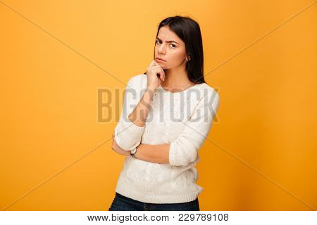 Portrait of a pensive young woman looking at camera isolated over yellow background