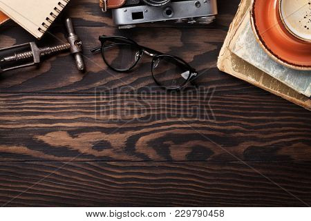 Retro table with vintage items. Old books, glasses, camera, coffee cup and wine corkscrew. Top view with copy space