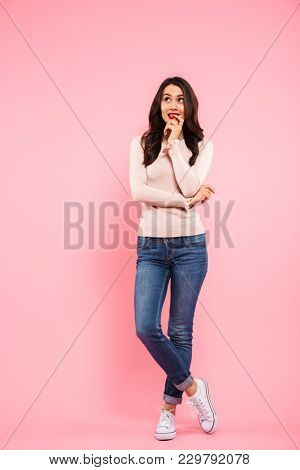 Full length photo of nice woman with long brown hair looking upward with guilty or shy sight isolated over pink background
