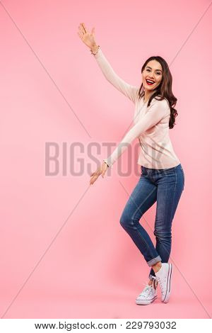 Full length photo of pretty woman with long brown hair wearing jeans showing big size of copyspace isolated over pink background