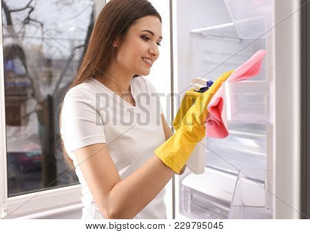 Woman cleaning empty refrigerator at home