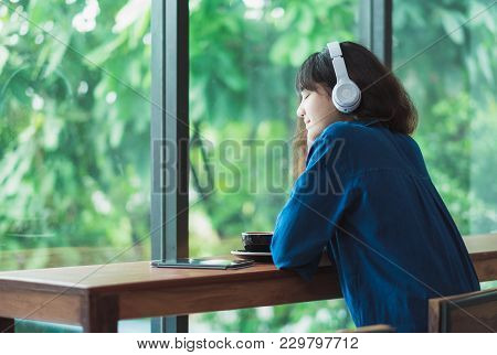 Happy Asian Casual Woman Listening Music With Headphones Near Window At Cafe Restaurant,digital Age