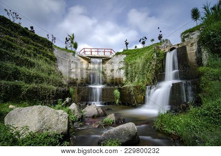Beautiful Scenery Of Hidden Waterfall With Cloudy Sky In The Middle Of Tea Farm At Cameron Highland,