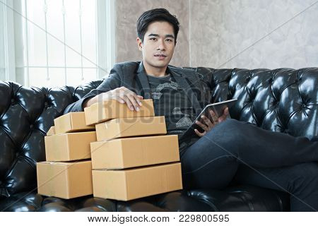 Start Up Small Business Entrepreneur Sme Freelance Asian Man Looking Tablet .  Young Asian Small Bus