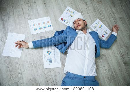 Business Man Fainted On Floor In Office. Unconscious Young Businessman Lying With Graphs And Charts