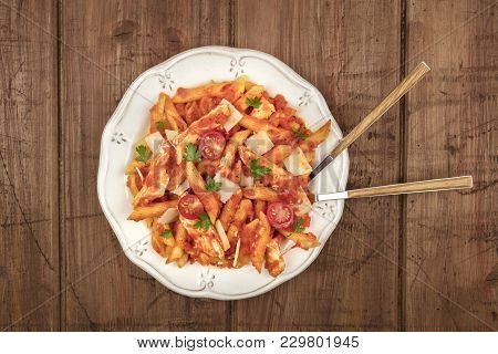 An Overhead Photo Of A Plate Of Penne Pasta With Chicken And Tomato Sauce, With A Fork And A Spoon P