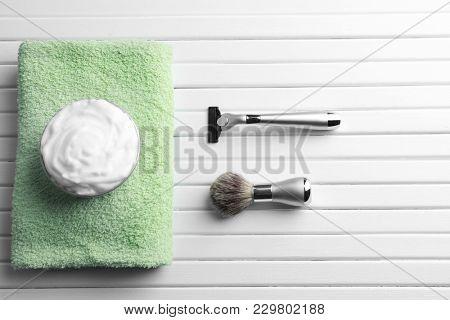 Barber brush, shaving foam and razor for man on wooden background