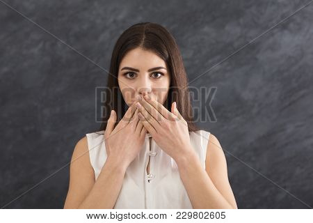Keep Silence. Scared Woman Covering Mouth With Hands While Posing To Camera On Gray Studio Backgroun